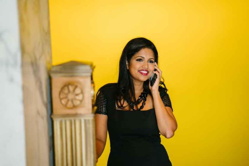 woman in black dress holding black phone